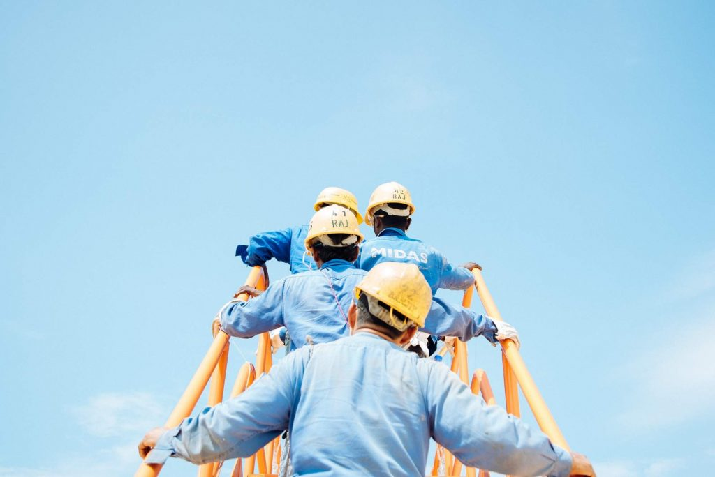Engineers climbing a bridge against a blue sky