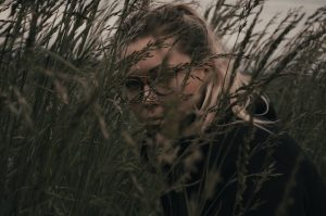 Woman's face obscured by long grass