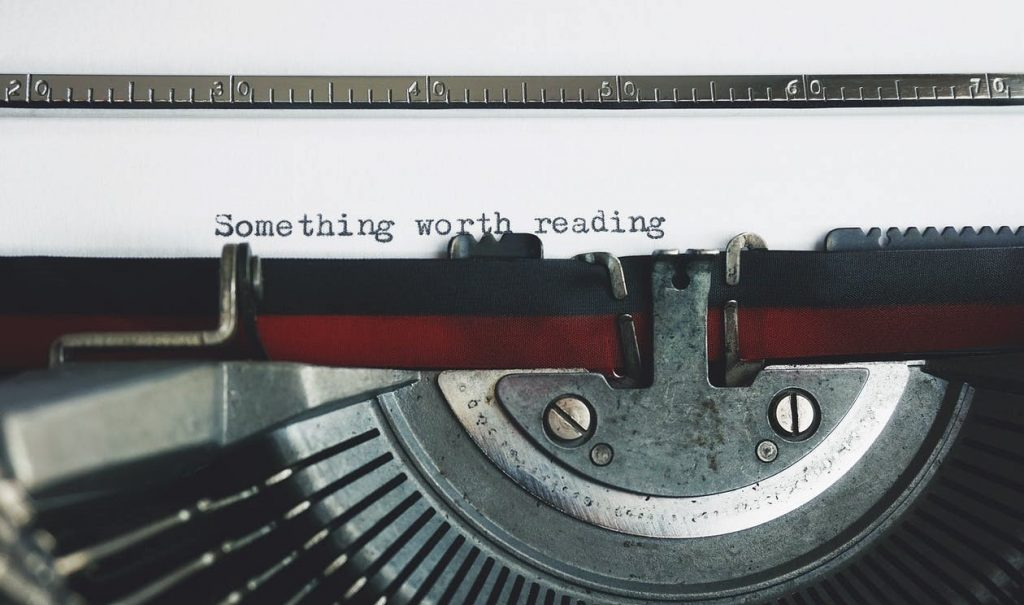 "Typewriter with paper displaying the words: ""Something worth reading"""