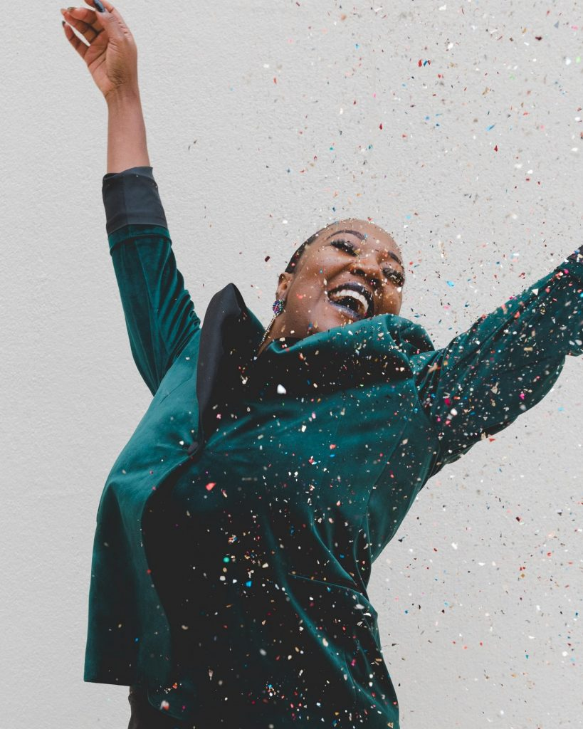 Woman celebrating by throwing confetti